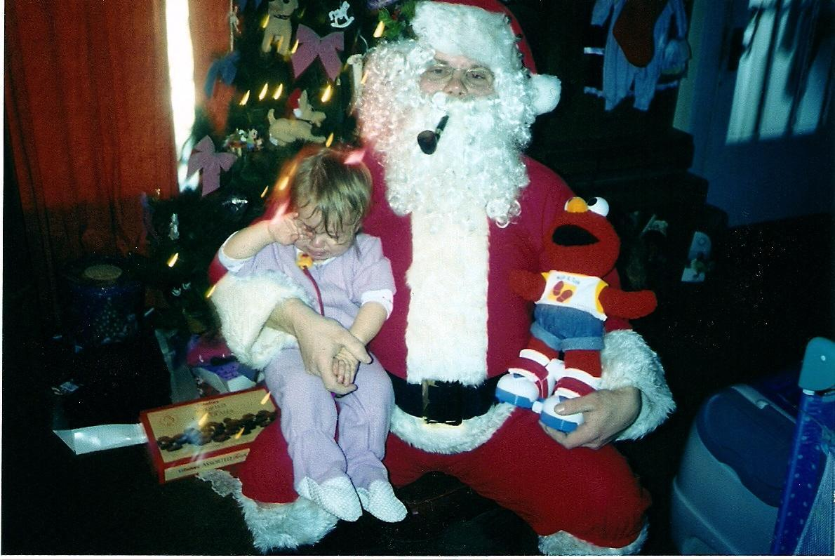 santa with his lil girl on his lap-not happy !  2