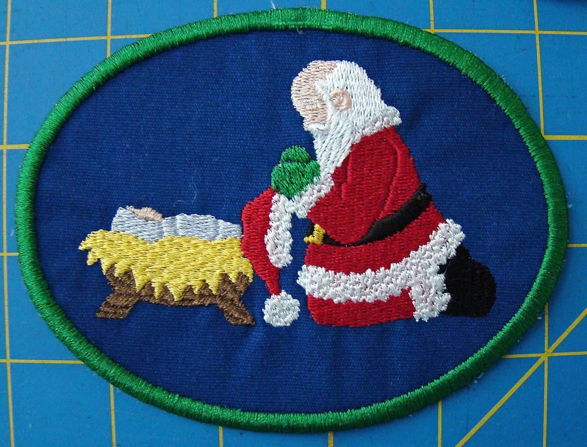 Santa kneeling at manger patch